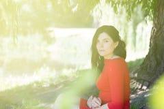 Madeiras vermelhas do verão do lago do parque do vestido do cabelo longo da menina foto de stock