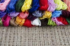 Madejas coloreadas de la mentira del hilo en un top de lino natural del fondo, fotos de archivo
