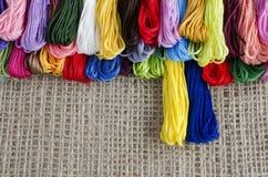 Madejas coloreadas de la mentira del hilo en un top de lino natural del fondo, fotografía de archivo