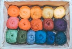 Madejas de hilos coloridos en colores calientes para el bordado y costura en la caja fotografía de archivo