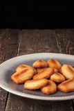 Madeleine cookies on the ceramic plate on the wooden table Stock Images