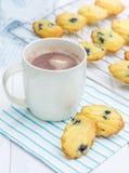 Madeleines avec des myrtilles et une tasse de chocolat chaud images stock