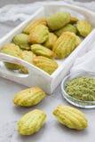 Madeleines faits maison de thé vert de matcha sur la table et dans le plateau en bois Image libre de droits