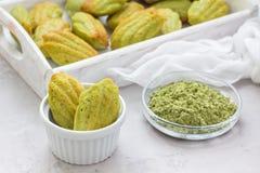 Madeleines faits maison de thé vert de matcha sur la table et dans le plateau en bois photos stock