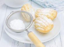 Madeleines in polvere zucchero sul piatto bianco Fotografia Stock