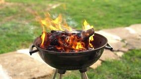 Madera ardiendo en la parrilla de la barbacoa, preparando los carbones calientes para asar a la parrilla la carne en el patio tra metrajes