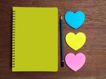 Madera con el cuaderno y efectos de escritorio amarillos imagen de archivo