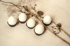 Madera contrachapada sin pintar con los huevos blancos en papel acanalado marrón Imagen de archivo libre de regalías
