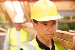 Madera de And Apprentice Carrying del constructor en emplazamiento de la obra fotos de archivo
