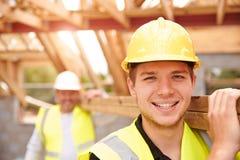 Madera de And Apprentice Carrying del constructor en emplazamiento de la obra fotografía de archivo