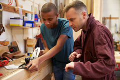 Madera de With Apprentice Planing del carpintero en taller imagen de archivo