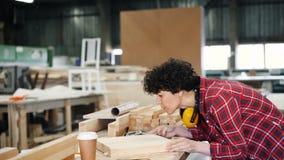 Madera de frotamiento del carpintero de sexo femenino con el pedazo de pulido de la herramienta abrasiva de madera almacen de video