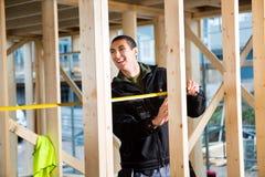 Madera de Laughing While Measuring del carpintero en el emplazamiento de la obra Foto de archivo