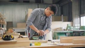 Madera de pulido del carpintero atractivo del hombre con la máquina que enarena que trabaja en taller almacen de metraje de vídeo