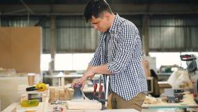 Madera de pulido del carpintero joven con la máquina eléctrica que trabaja en la tabla solamente almacen de metraje de vídeo