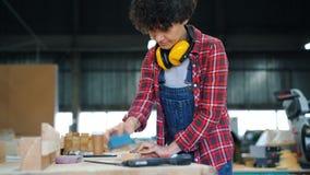 Madera de pulido del carpintero de sexo femenino con el bloque abrasivo que trabaja en taller solamente almacen de metraje de vídeo