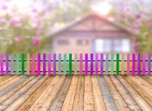 Madera de madera Varicolored de la cerca y del piso con la casa borrosa en th foto de archivo