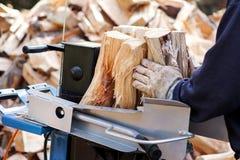 Madera del corte de la sierra para el invierno Una leña del corte del hombre para el invierno usando una madera de construcción m fotos de archivo