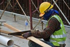 Madera del sawing del carpintero en el emplazamiento de la obra Foto de archivo