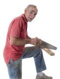 Madera del sawing del hombre mayor Fotografía de archivo
