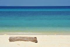 Madera en una playa arenosa blanca. Fotografía de archivo libre de regalías