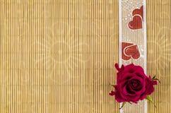 Madera, fondo de mimbre con la cinta del corazón y flor color de rosa Fotos de archivo