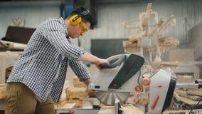 Madera que asierra del hombre en taller usando la sierra eléctrica que trabaja gafas solamente que llevan almacen de video