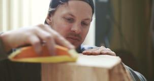 Madera que enarena del carpintero joven en taller almacen de video
