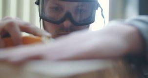 Madera que enarena del carpintero joven en taller almacen de metraje de vídeo