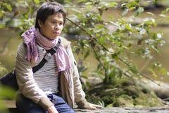 Madera que se sienta del hombre vacante de Asia en bosque del río Imagen de archivo libre de regalías