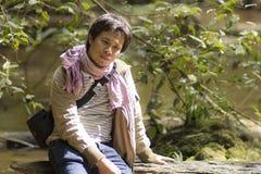 Madera que se sienta del hombre vacante de Asia en bosque del río Imágenes de archivo libres de regalías