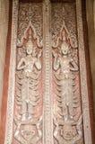 Madera que talla imágenes en las puertas del templo de Phra Kaew del espino en Vientián, Laos Imagen de archivo