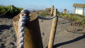 Madera y cerca de la cuerda en la playa imágenes de archivo libres de regalías