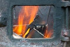 Madera y el fuego en el horno con las chispas del vuelo Imagen de archivo libre de regalías