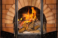 Madera y fuego acogedores de la rejilla de la chimenea del ladrillo imagen de archivo