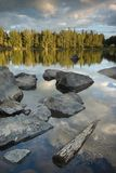 Madera y piedras en el lago imagen de archivo