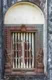 Window frame on Mausoleum at Raja Tomb domain, Madikeri India. Madikeri, India - October 31, 2013: Closeup of window and rusty decorated metal frame of Royal stock image