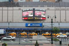 Madison Square Garden. NEW YORK, USA - JULY 1, 2013: People walk by rainy Madison Square Garden in New York. MSG is one of most popular multi-purpose indoor Stock Photo
