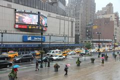Madison Square Garden. NEW YORK, USA - JULY 1, 2013: People walk by rainy Madison Square Garden in New York. MSG is one of most popular multi-purpose indoor Stock Image