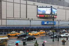 Madison Theater. NEW YORK, USA - JULY 1, 2013: People walk by rainy Madison Square Garden in New York. MSG is one of most popular multi-purpose indoor arenas in Stock Photography