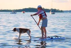 MADISON, WI - 3 luglio 2014: Imbarco della pagaia di Brett Hulsey con il suo penny del cane Fotografie Stock