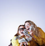 Madly happy girls with money. Two madly screaming girls with money  over blue background Stock Photography