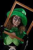 Madly leprechaun behind a wooden frame, black background Royalty Free Stock Photos