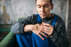 Madman in uniform with plasters on face and hands Stock Photography