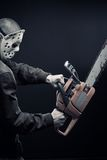 Madness. Guy with bloody chainsaw posing over dark background stock image