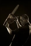 Madness. Maniac in mask with chainsaw posing over dark background stock image