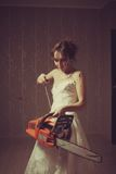 Madness. Crazy bloody bride with chainsaw. Indoors shooting stock photo