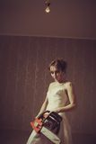 Madness. Young bride with bloody chainsaw. Indoors shooting royalty free stock image