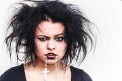 Madness. Mad girl with dark makeup and crazy hair holding a cross nacklace in the mouth Stock Images