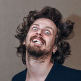 Madness. Man in a state of madness, shaggy with a grin on his face stock photos